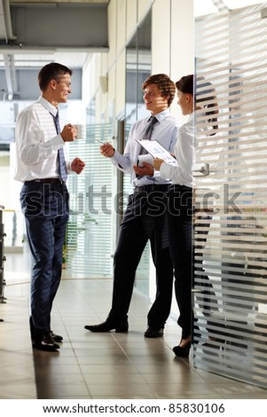 Three colleagues communicating and laughing in office - stock photo