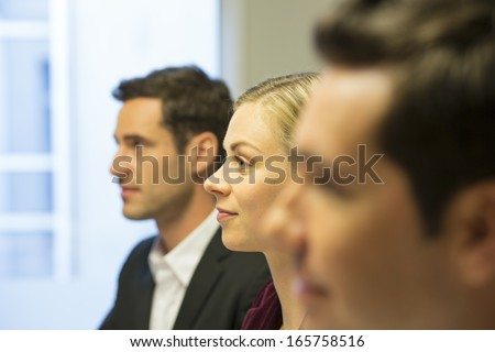 Three colleagues sitting at a business meeting, focus on pretty woman - stock photo