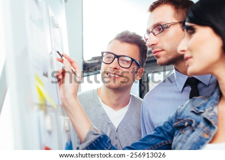 Three colleagues standing in front of a board and writing something on it - stock photo