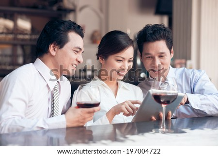 Three colleagues using digital tablet in the bar