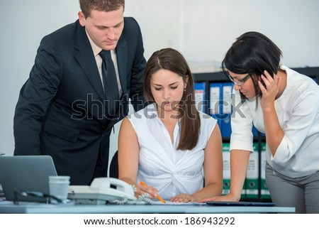 Three colleagues working in modern office