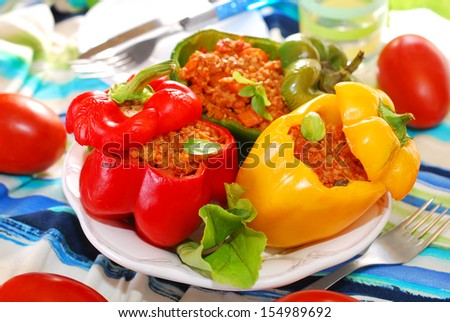 three color bell peppers baked and stuffed with minced meat and vegetables