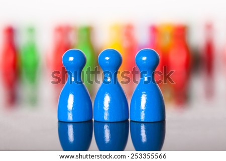 Three colored ludo figures in front of many others.  three blue figures in  in a row. Figures in the background unsharp.Bokeh. - stock photo