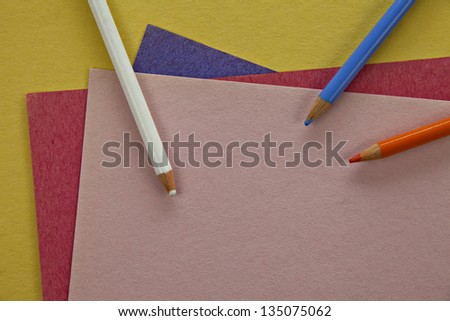 Three colored pencils on colorful paper - stock photo