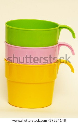 Three colored plastic cups isolated over white background
