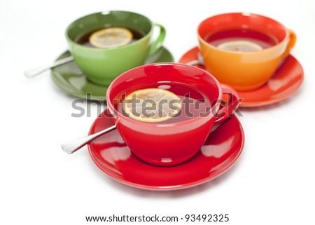 Three colored tea cups with tea and lemon - stock photo