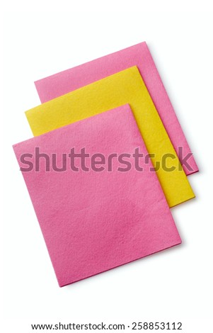 Three colorful absorbent kitchen cloths in pink and yellow in a household chores and hygiene concept, overhead view on white - stock photo