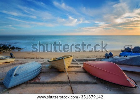Three colorful boats resting on the shore. On the background a sea landscape.