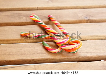 Three colorful candy sticks on wooden table