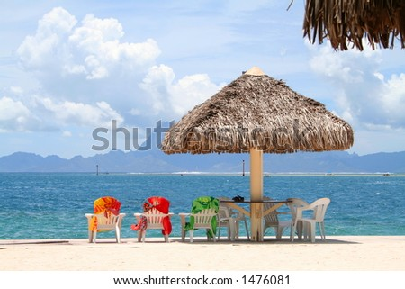 Three colorful chairs aligned on a beach in Tahiti, French Polynesia - stock photo
