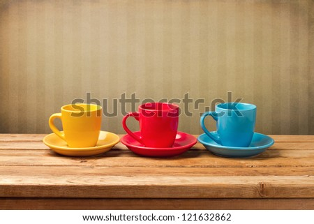 Three colorful coffee cups over vintage background - stock photo