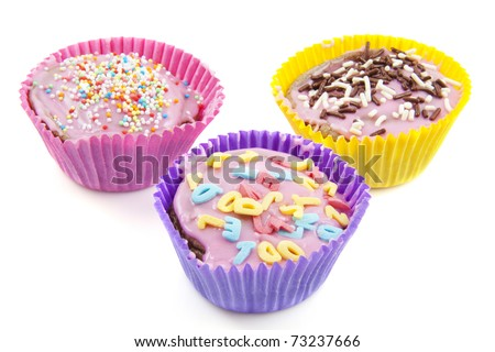 Three colorful decorated cupcakes isolated over white - stock photo
