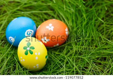 Three colorful Easter eggs on a fresh green grass - stock photo