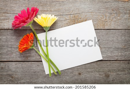 Three colorful gerbera flowers and blank greeting card on wooden table - stock photo