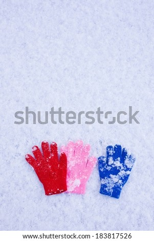 Three colorful gloves are lying in the snow. - stock photo