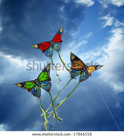Three colorful kites at cloudy sky - stock photo