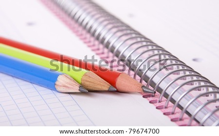 Three colorful pencils on a open notebook - stock photo