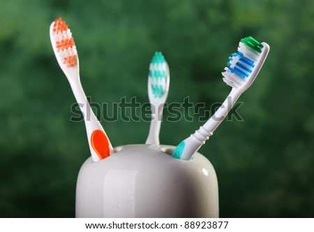 Three colorful toothbrushes in holder - stock photo
