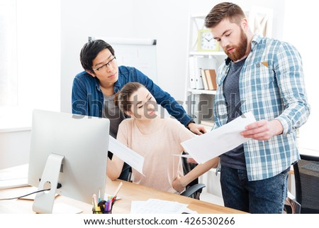 Three concentrated young businesspeople working with documents and using computer in offie together - stock photo