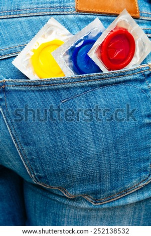 Three condoms in a jeans pocket.