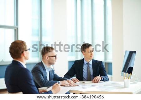 Three confident businessmen sitting in front of pc in office - stock photo