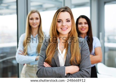 Three confident female managers standing and looking at the camera - stock photo