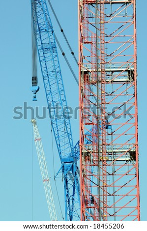 Three construction cranes reaching to the sky, in the colors of the U.S. flag - stock photo