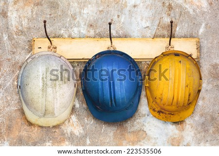 Three construction helmets hanging on an old wooden hat-rack - stock photo
