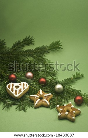 Three cookies and five shiny balls on fir branch isolated on green paper - stock photo