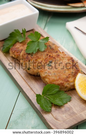 Three crab cakes appetizer with spicy sauce and fresh parsley. Dungeness crab in the background. - stock photo