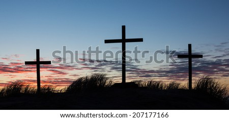 Three crosses on a hill with a wonderful sunset sky behind them.