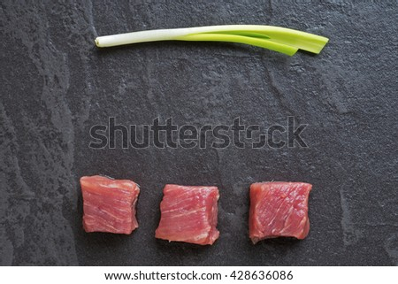 Three cubes of meat and green onions on the black stone table - stock photo