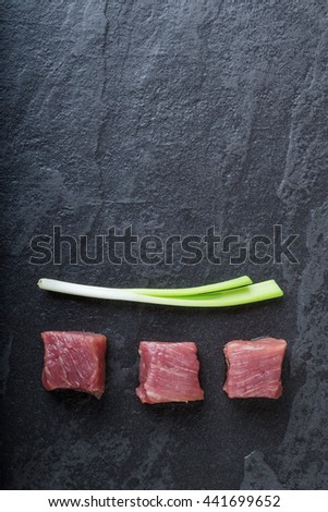 Three cubes of meat and green onions on the black stone table