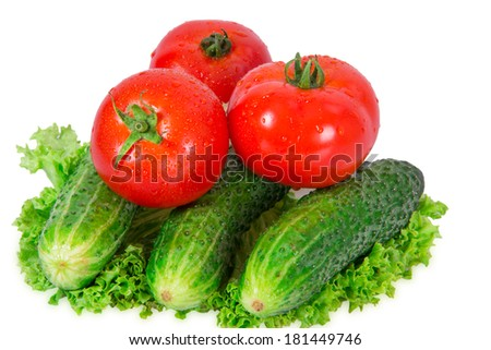 Three cucumbe  and three tomatoes  lie on lettuce leaf on a white background - stock photo