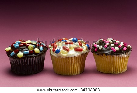 Three cupcakes decorated with pills, close-up
