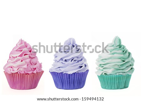 Three cupcakes in a row isolated on a white background - stock photo