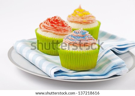 Three cupcakes on plate with sprinkles on them