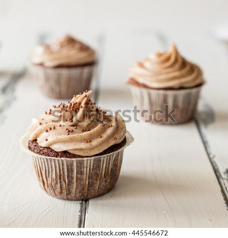 Three cupcakes on white wooden - stock photo