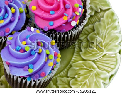 Three Cupcakes with purple and pink frosting and sprinkles - stock photo