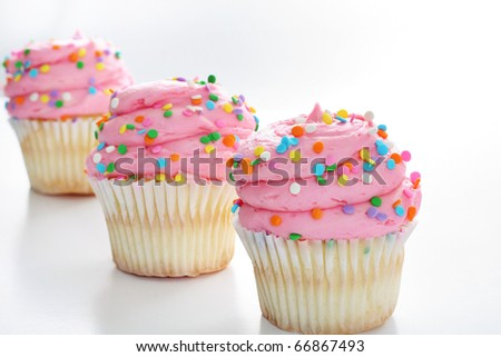 Three cupcakes with sprinkles in a line