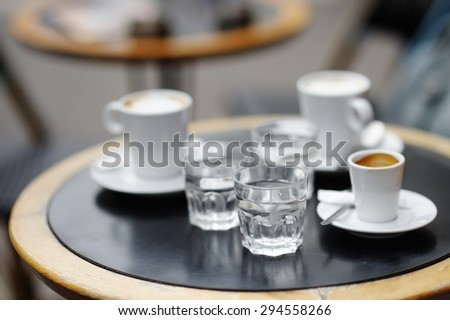 Three cups of fresh coffee (espresso and latte) and three glass with still water on table of Parisian outdoors cafe  - stock photo