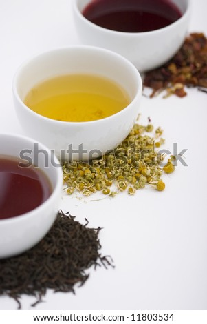 Three cups of tea in different colors with three different types of herbs on piles - stock photo