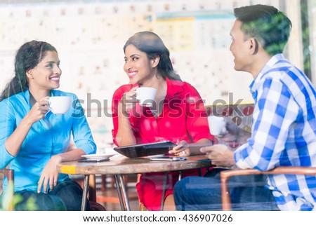 Three customers at coffee shop, having coffee, view through shop window - stock photo
