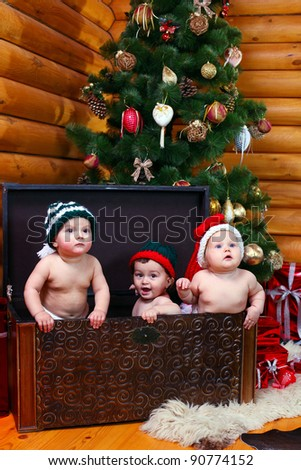 Three cute babies in xmas hats inside large chest - stock photo