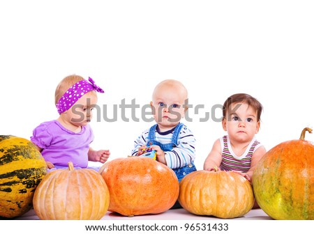 Three cute babies sit behind large pumpkins