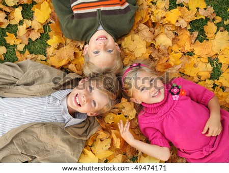 three cute caucasian kids lying on fall leaves outdoors - stock photo
