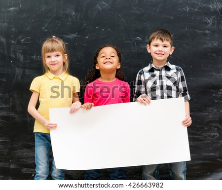 three cute children holding an empty paper sheet for ad with chalky blackboard on background - stock photo