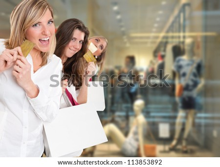 Three cute girls holding credit cards at the mall - stock photo