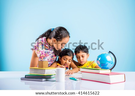 three cute indian kids studying, smart asian girls and boy doing home work, indian siblings studying, indian small girl helping her brother and sister in doing homework - stock photo