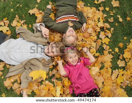 three cute kids playing in leaves looking upwards - stock photo